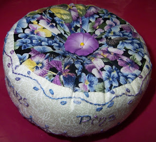 Pincushion made from pansy fabric with embroidery around the sides and a pansy button in the center of both top and bottom