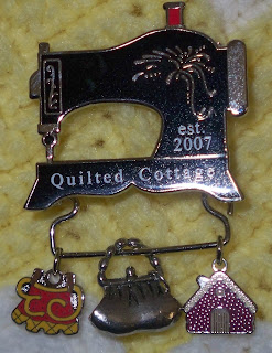Quilted Cottage pin which is a sewing mach8ine with three charms attached to a bar beneath the machine