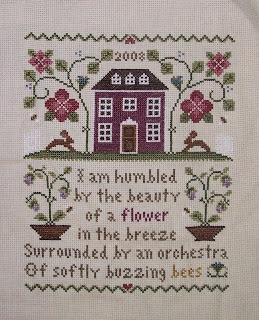 cross stitch sample of house and flowers with verse