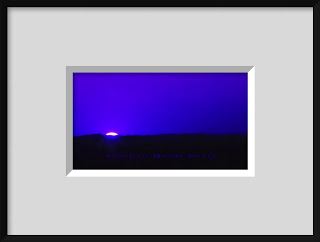 A framed photo of a glowing blue moonrise is an abstract explosion of color with a silhouette of the horizon.