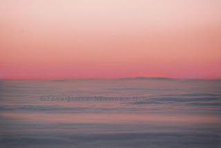 A blanket of fog rests silently over the High Plains of Colorado as the sunrise turns pink
