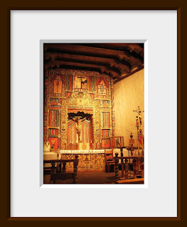 An ornate Spanish altar in a historical southwestern mission is rich in warm colors of orange, red, and gold and glows in the soft light.
