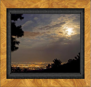 Framed photo of the autumnal full moon rises over the city of Fort Collins on the high plains of Colorado casting a glowing blush in the sky of pink, mauve, and lavender.