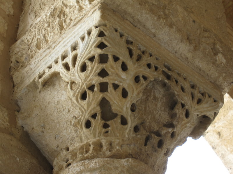column capital, probably Byzantine, in the Great Mosque at Kairouan.  It's been reused and has areas gouged out of it – probably those areas had figures, which aren't allowed in Islamic decoration, so they were removed before the capital was reused.