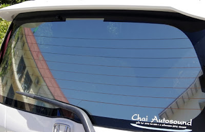 Blue Skies reflected in rear window of Honda Jazz