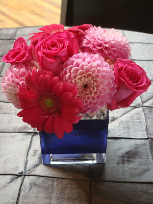 Centerpieces of gerber daisies dahlias roses hydrangea placed in cube