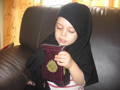 Muslim Baby Girl Holding Holy Quran photo