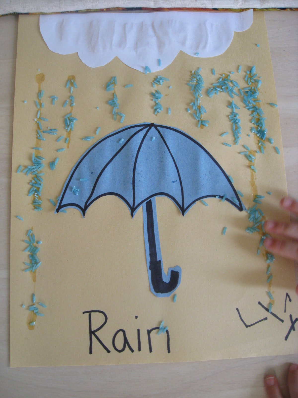 Cut out construction paper umbrella. Have child glue to paper.