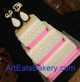 Three tier square fondant wedding cake with pink ribbons