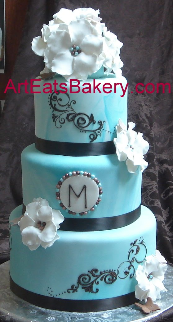 Blue marbled fondant round wedding cake with brown scroll work monogram
