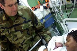 El ginecólogo militar José Sánchez Jordá observa al bebé recién nacido en el barco español- RAMÓN LOBO