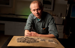 El investigador Michael I. Coates, junto a un fósil de un tiburón. Janson Smith