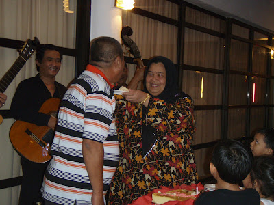 Loving wife giving the first bite to Pak Hasan