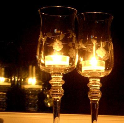 Glas med fyrfads-lys i vinduet