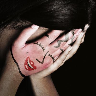 Pige med smil malet på hånd, der dækker nedbøjet ansigt