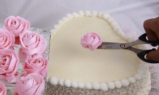 Ambil hiasan mawar dengan gunting. Pindahkan ke atas kue tart yang ...