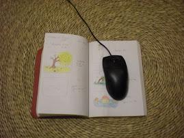 Anaîs utilise une souris d'ordi sur un carnet de notes