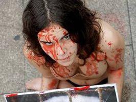 chica con maquillaje simulando sangre, con pancarta, en ropa interior