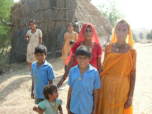 Rajasthani desert family in front of grass hut