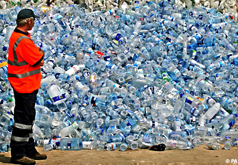 a man stands in front of a huge pile of empty plastic water bottles