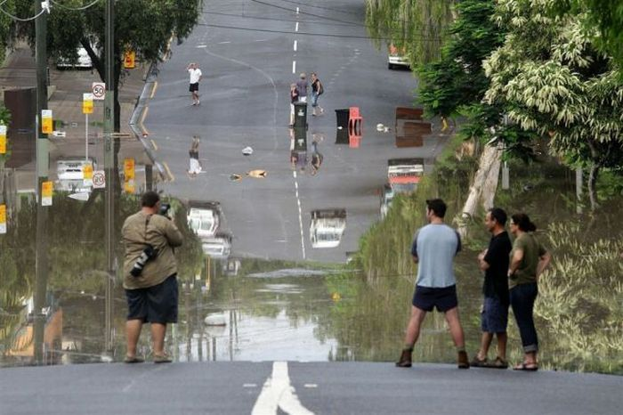 people standing on a road looking across to people on the other side over floodwaters