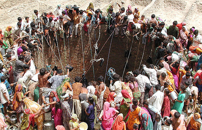 a crowd of people around a well in India during a drought