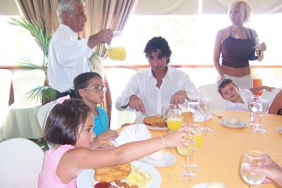 Dani comiendo con los demás niños, mientras Fali le corta la carne