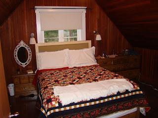 How to Paint Over Varnished Wood- A dark wood wall with a bed in front of it.