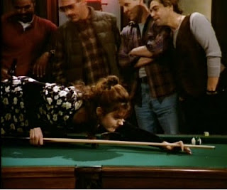 Daphne leans over to take her shot; the other players are distracted.