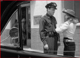 John Dall exits the bank as Peggy tries to sweet talk the cop - all from the back seat of the getaway car