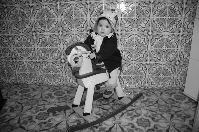 Criança no cavalo de madeira
