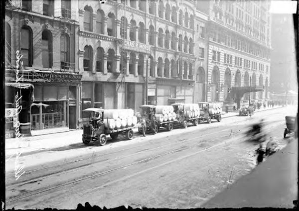 4 Chicago Daily News paper trucks parked along the curb of W. Madison St. Chicago 1912