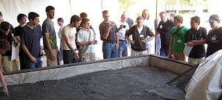 Teams, Engineers, and Scientists inspect the lunar sandbox prior to the 2008 Regolith Excavation Challenge. Photo Credit: CSA