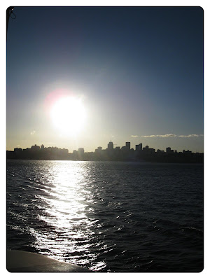 sun on the water behind the sydney harbour bridge