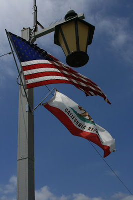 American and Californian flags flying over Stearns Wharf