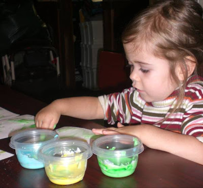 Preschooler with homemade eatable finger paints.