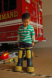 David Cheng, 3, is trying out fire fighter bunker rubber boots for size at the Ballston Fire Station in Arlington