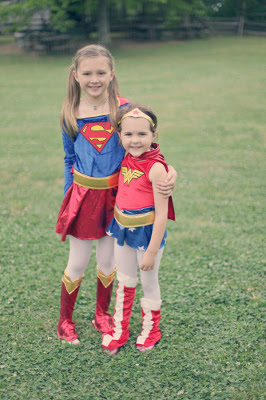 a girl dressed as Superman and another girl dressed as Wonderwoman