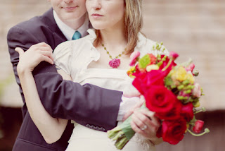 man holds woman who has bouquet of flowers in hand