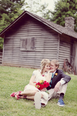 couple nestles up to each other on grass and woman who has bouquet of flowers in hand