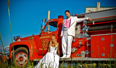 bride sits and groom stands on a red firetruck