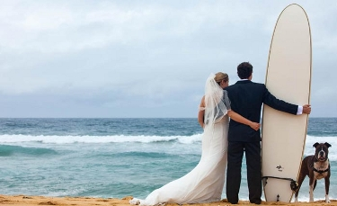 The back of a bride in her gown with her arm around the waist of the groom who is holding a surf board, and is next to a dog, as the couple looks at the ocean