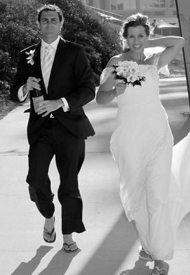 Black and white photo of the bride with bouquet in hand and groom, both in wedding attire and flip-flops