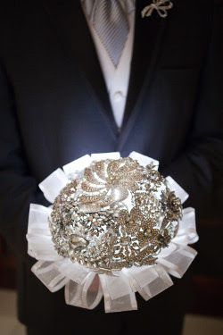 headless man holding white crystal brooch bouquet
