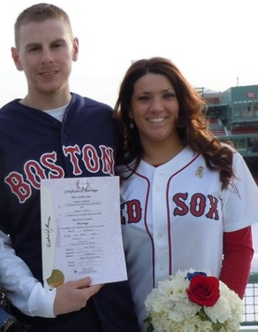 Man in shirt that says Boston, with arm around woman wearing shirt with words Red Sox and holding flowers