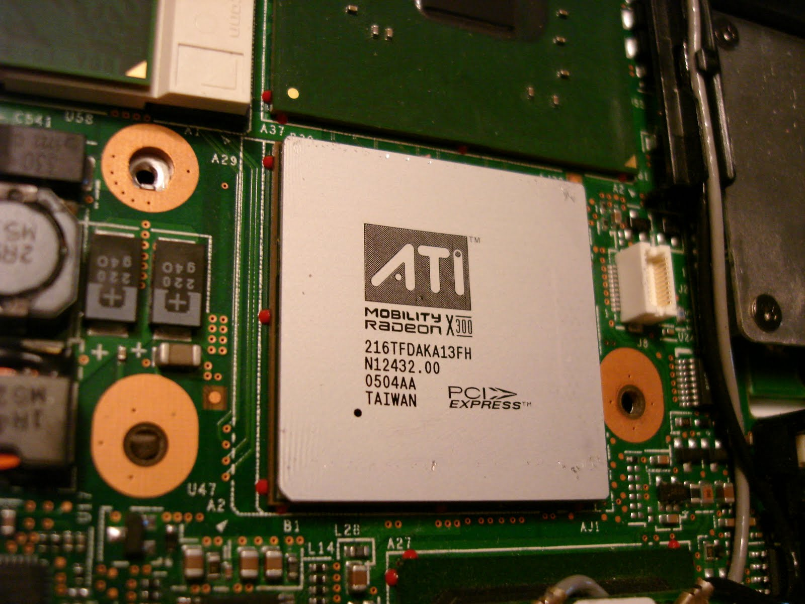 The ATI GPU with the heatsink removed. Notice the red epoxy dots around the  edges of the GPU and the South and Northbridge chips. The epoxy, in  addition to ...