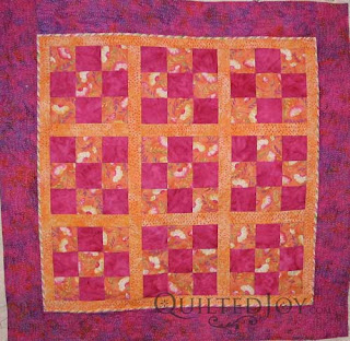 Colorful Coneflower Batik quilt, quilted by Angela Huffman