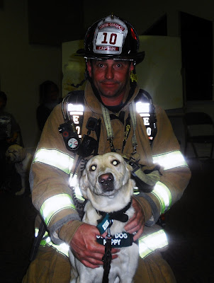 A firefighter in full gear on his kneeling down with Reyna sitting between his knees