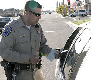 A CHP officer giving a driver a citation.