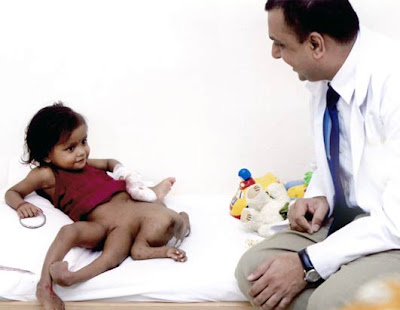 Lakshmi Tatma lying on examination table chatting with a doctor